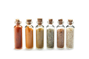 Row of small glass bottles with different spices on white background