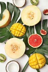 Flat lay composition with melon and other fruits on white background