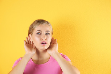 Young woman with hearing problem on color background. Copy space text