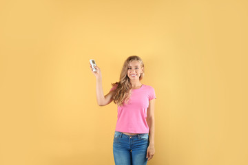 Young woman with air conditioner remote on color background