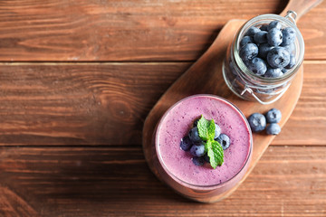 Glass of smoothie and jar with blueberries on wooden background, top view. Space for text