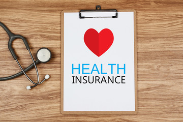 Clipboard with text Health INSURANCE and paper heart with stethoscope on wooden desk, Healthcare and Medical Concept