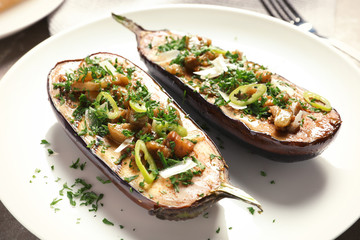 Plate with tasty stuffed eggplants, close up view