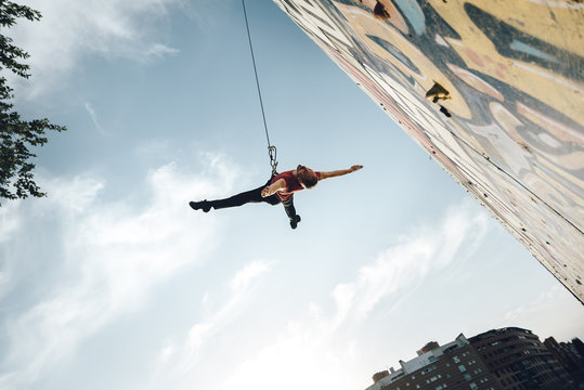 Dancer performing aerial dance on urban scenery at sunset against blue sky