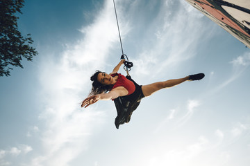Sexy dancer performing aerial dance on urban scenery at sunset against blue sky