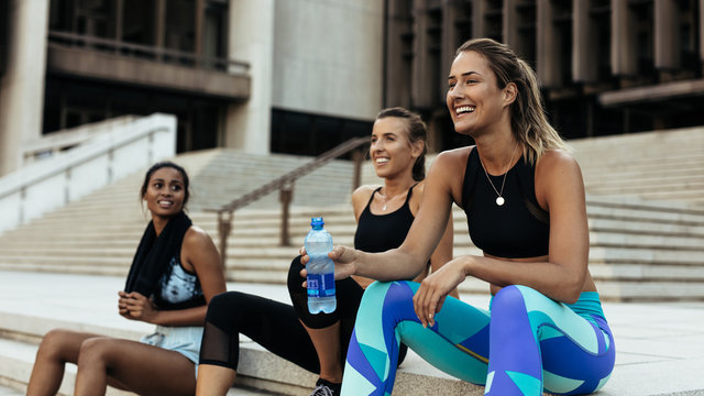 Women relaxing after workout sitting on stairs
