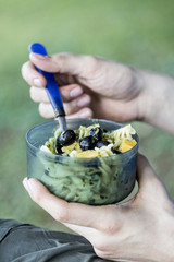 Simple tasty traveler's dinner, pesto pasta with olives, outdoor cooking equipment