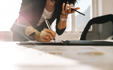 Businesswoman making notes standing at her desk in office