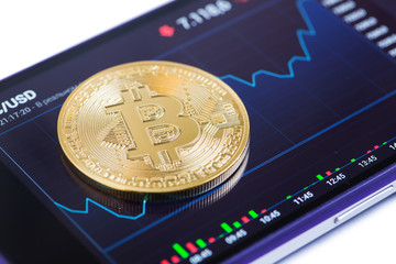 Golden bitcoin against currency chart on smartphone