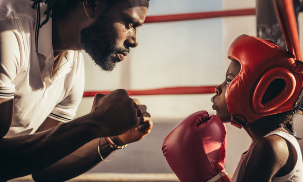Boxing trainer teaching a kid about boxing
