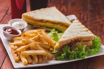 Club sandwich served with french fries and soda