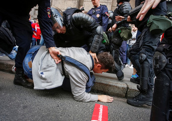Police officers detain a protester during a rally against planned increases to the nationwide pension age in St. Petersburg