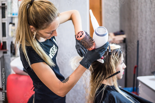 The Hairdresser Dries Hair With A Dryer Client