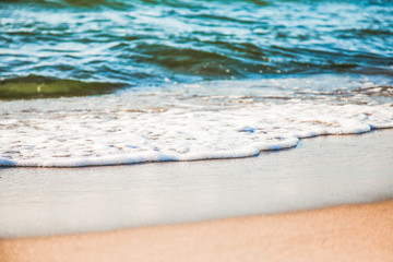 waves of pure azure water with white foam on yellow sand on a sunny day, close up blurry background