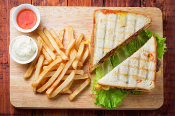 Club sandwich served with french fries on wooden backgorund