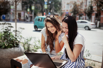 On a mild day, two cute slim girls with long dark hair,wearing casual style,sit on the bench and look attentively at the laptop screen.