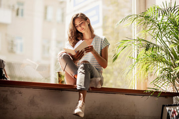 A pretty slim young girl with long hair,wearing casual outfit,sit on the windowsill  and reads a book in a cozy cafe.
