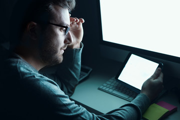 Man in front of computer monitor at night