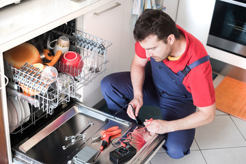 Worker repairing the dishwasher in the kitchen