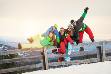 Happy friends skiers and snowboarders sunset mountains