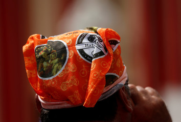 A cyclist wears a bandana with holy pictures at the end of the annual bicycle and motorcycle pilgrimage during the Our Lady of Graces feast in Zabbar