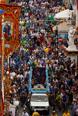 Cyclists follow a truck carrying a painting of Our Lady of Graces, the patron of Maltese cyclists and motorists, during the annual bicycle and motorcycle pilgrimage during the feast of Our Lady of Graces in Zabbar