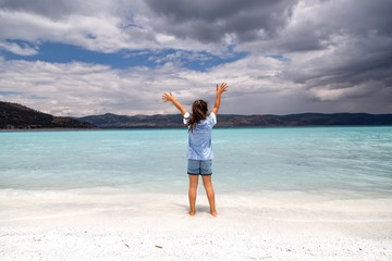 girl standing near turquoise lake