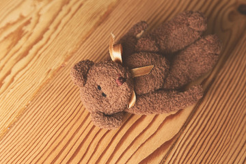 A brown teddy bear lying on a wooden surface. This image can be used to represent the concept of childhood.
