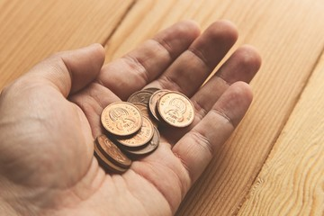 A hand holding a bunch of South African 5 cent coins (money).