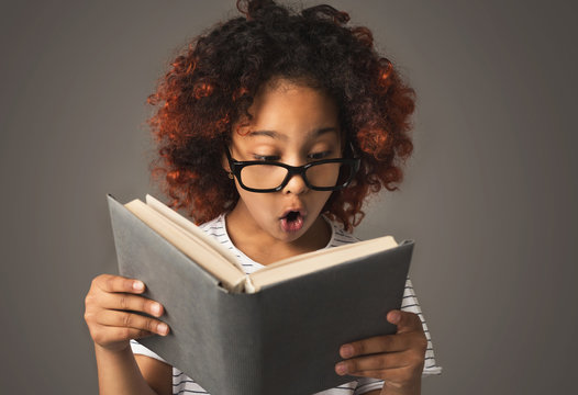 Surprised little black girl with book at gray background