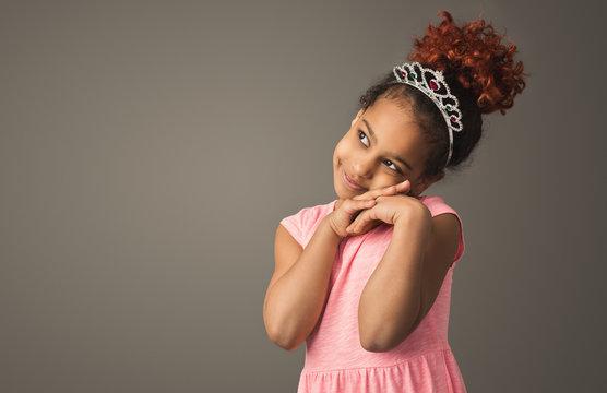 Little black girl dreaming, wearing tiara