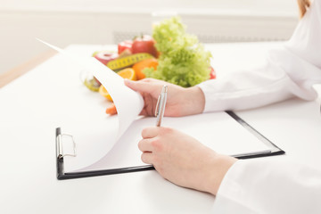 Nutritionist doctor writing diet plan on table