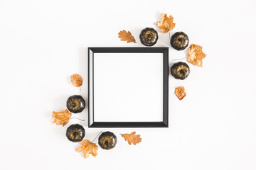 Autumn composition. Photo frame, leaves, pumpkins on white background. Autumn, fall, halloween concept. Flat lay, top view, copy space, square