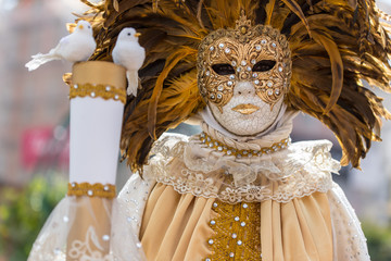 a woman in a mask and a white Venetian costume in the carnival