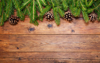 Christmas wooden background with fir branches and cones, top view