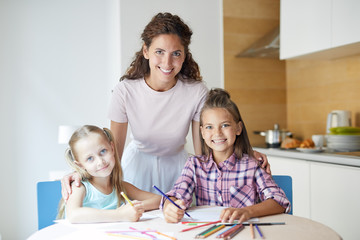 Two little girls drawing with crayons with their mom between them and all looking at camera