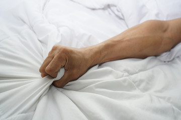 hand of men pulling white sheets in ecstasy, orgasm.