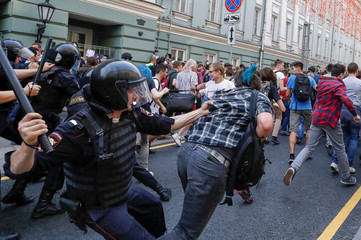 Police officers chase protesters during a rally against planned increases to the nationwide pension age in Moscow