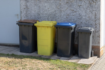 Different dustbins in front of a wall of a house