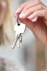 Frau hält Schlüssel in ihren Fingern