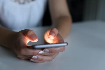 Frau tippt nachts auf Smartphone