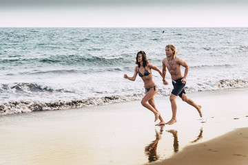 couple of friends with relationship run together on the shore near the ocean and the waves enjoying the summer holiday. blue sky from evening. young beautiful people in outdoor leisure activity.