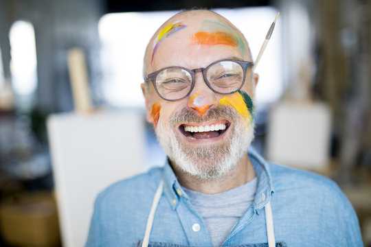 Bald mature artist with grey beard and paints all over his face looking at camera