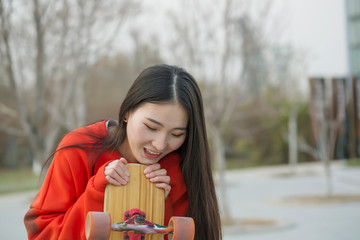 Young skateboard girl holding her longboard outdoors. Portrait, Skateboard Girl