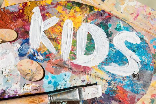 Words kids painted with white gouache on palette of artist with mixture of colors