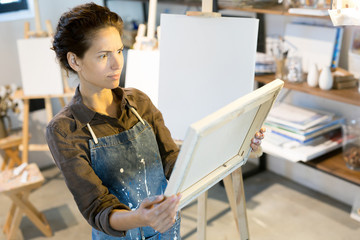 Amazed or shocked young painter looking at painting on easel with her eyes wide open