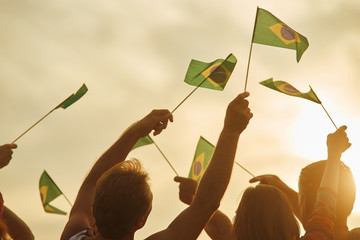 Brazilian patriots with flags outdoor. Silhouette of patriotic brazilian family, rear view.