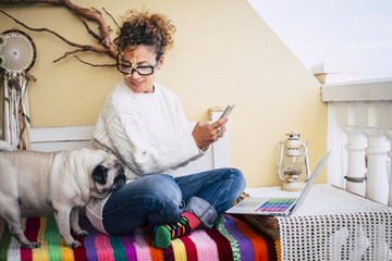 Happy alternative young cheerful woman warking at home with a new business way. sitting on a bench outdoor at home with best friend old pug together. colorful bench and lifestyle. laptop and phone