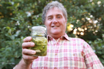 Man holding refrigerator cucumber pickles in a jar outdoors