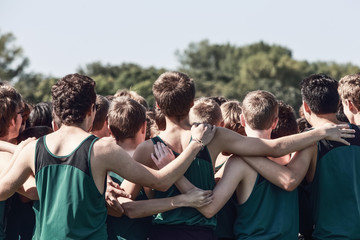 Boys on cross country team in a huddle
